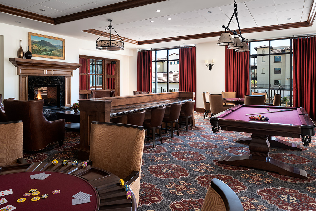 Game room with card table, pool table, and fireplace with seating.