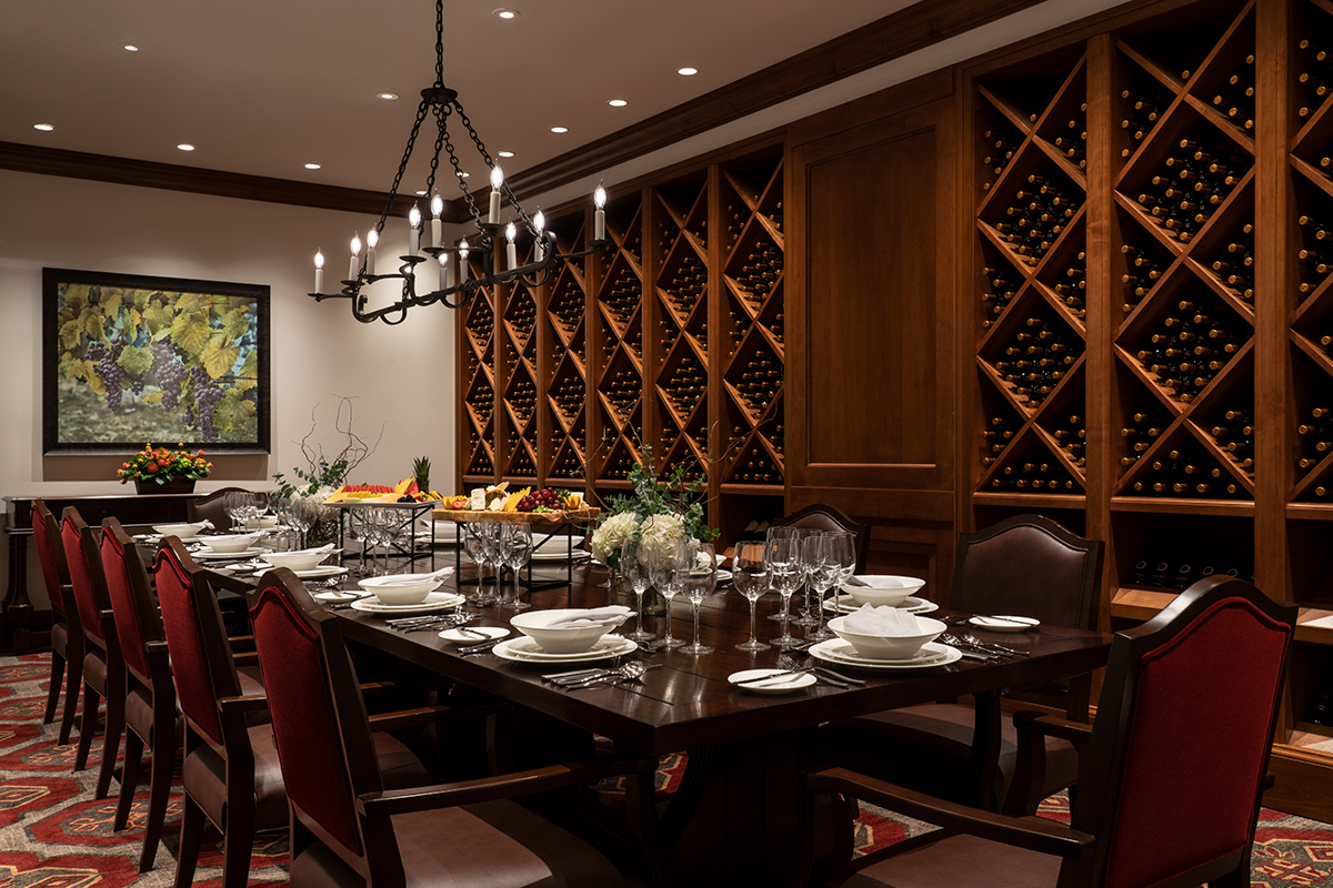 Private dining with large table set with food and wine bottles filling the wall.