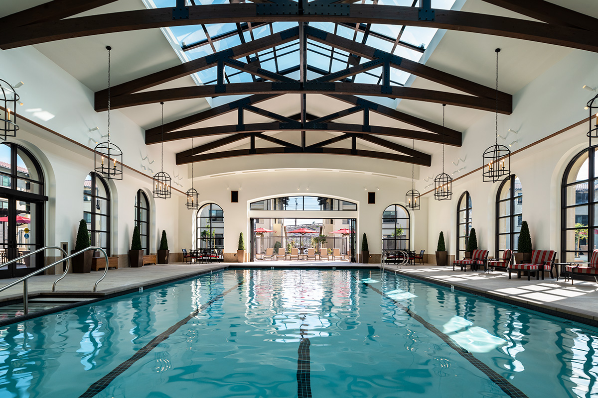 Large pool area with wood beams above it and chandeliers hanging on the sides.