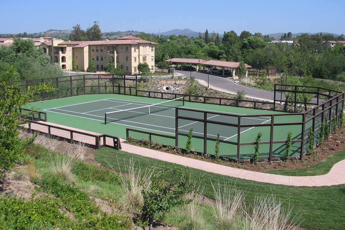 Large, outdoor tennis court.
