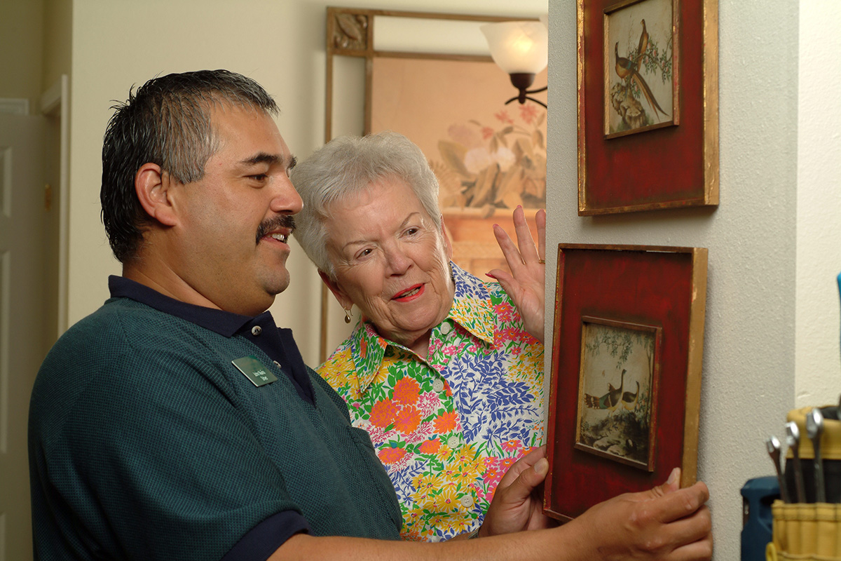 Handyman helping a resident hang pictures on her wall.