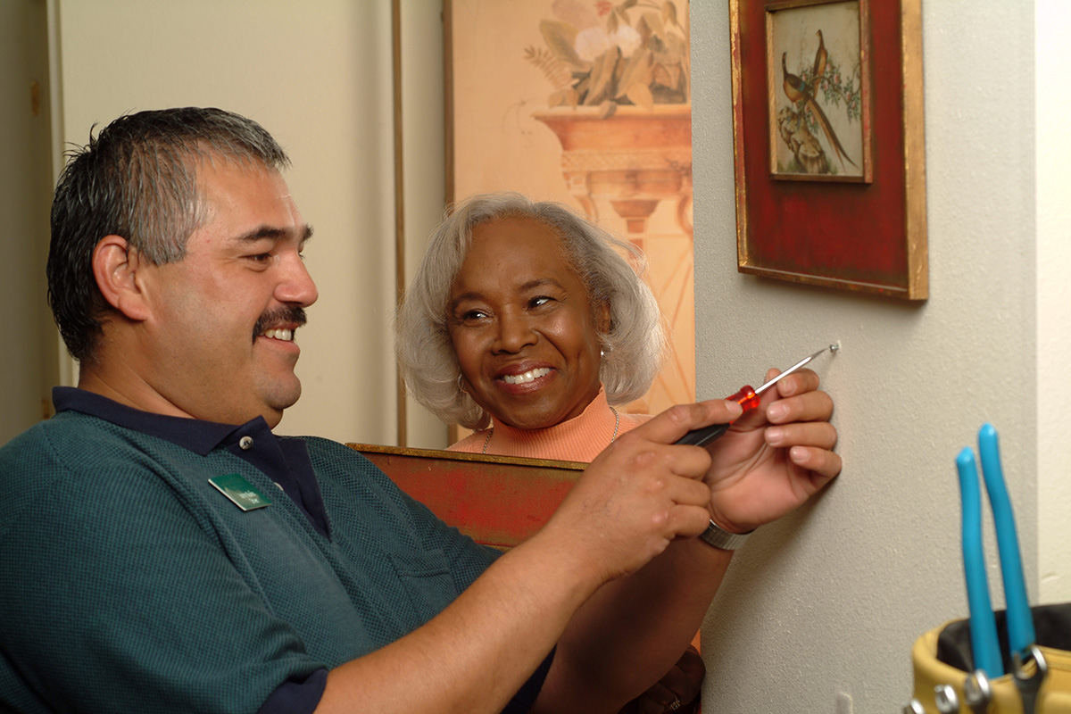 A handyman helping a resident hang up art in her home.