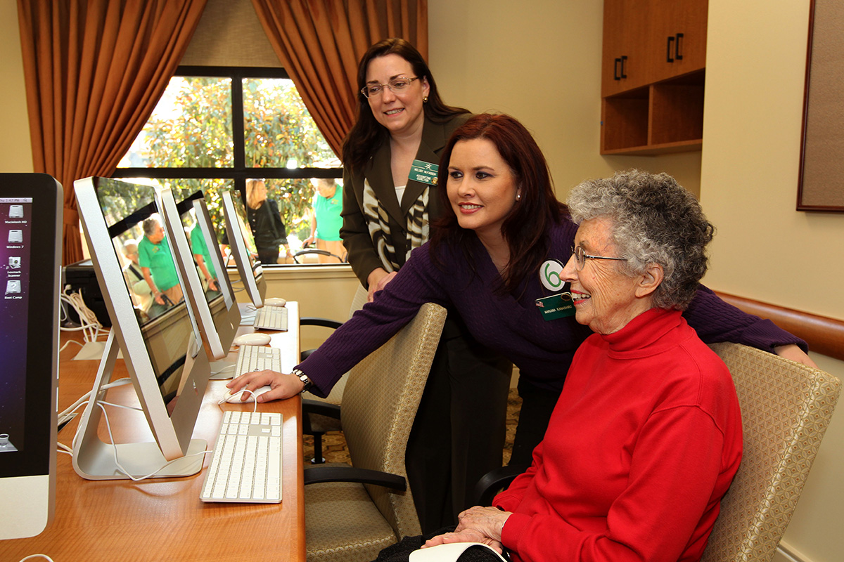 A resident working with staff on how to use the computer.