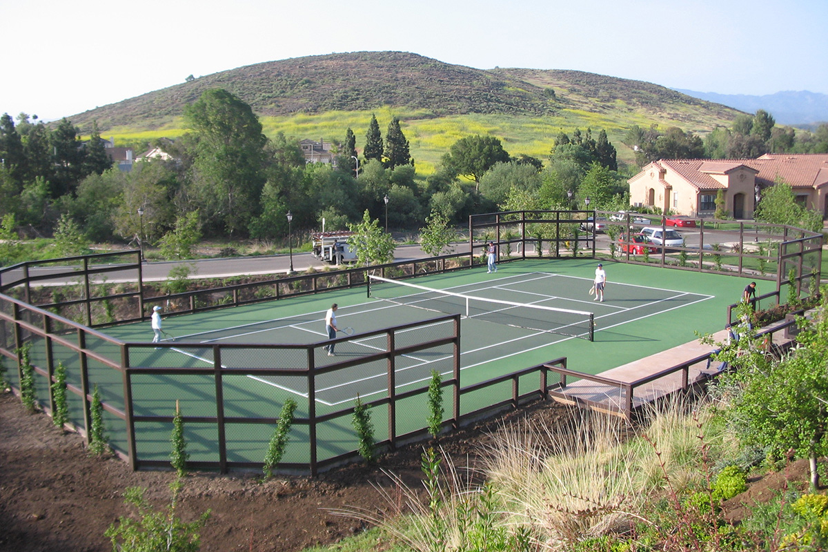 Large tennis court with mountains in the background.