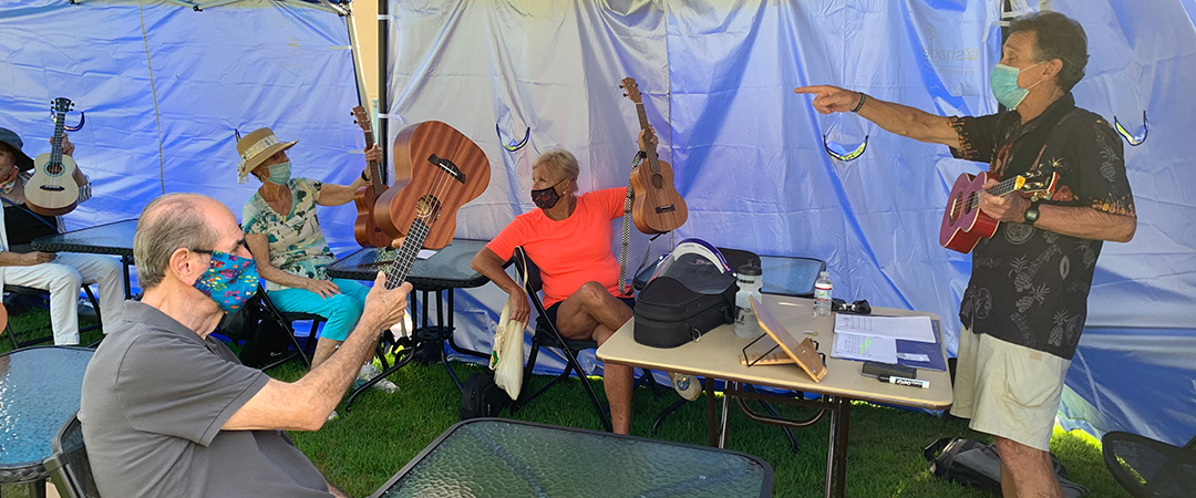 Residents playing ukulele's outside with instructor.