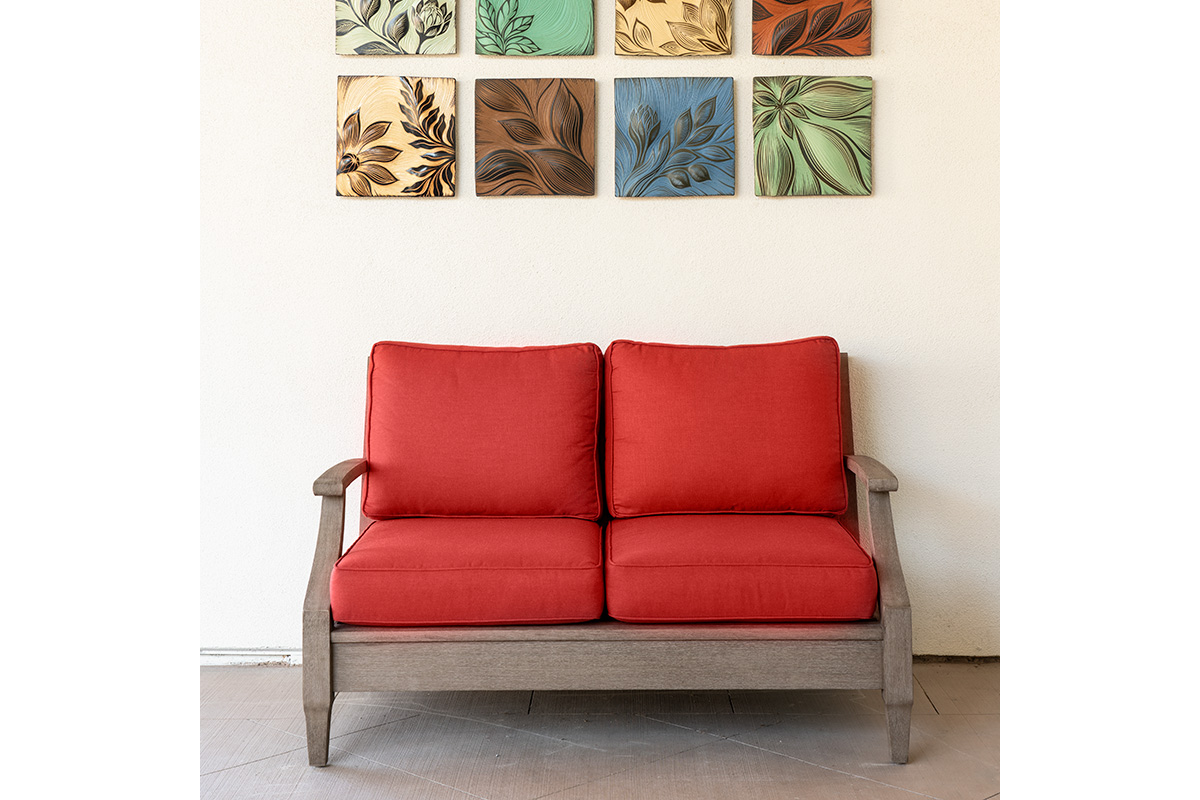 Red couch with multi colored pictures above it
