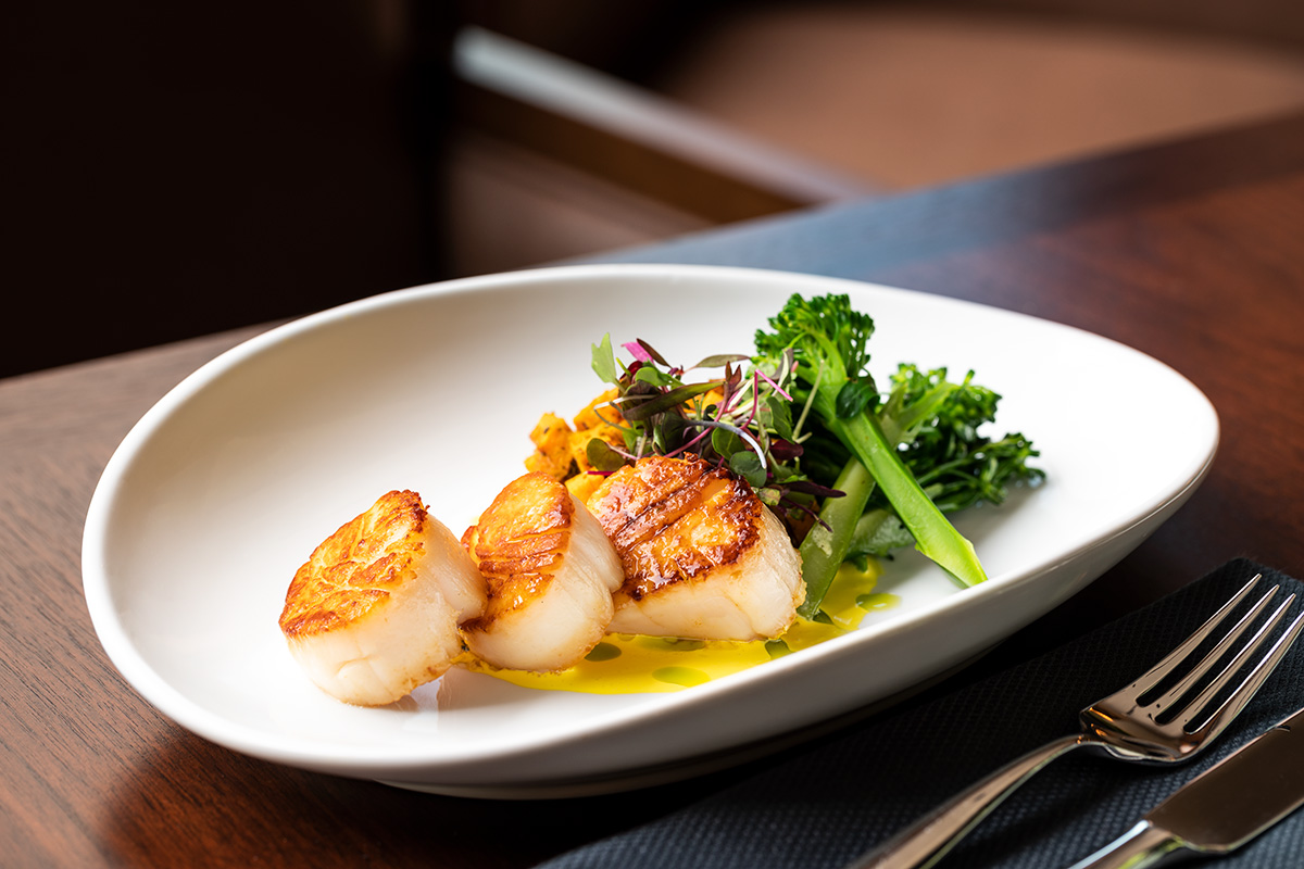 Delicate scallops in butter garnished with vegetables