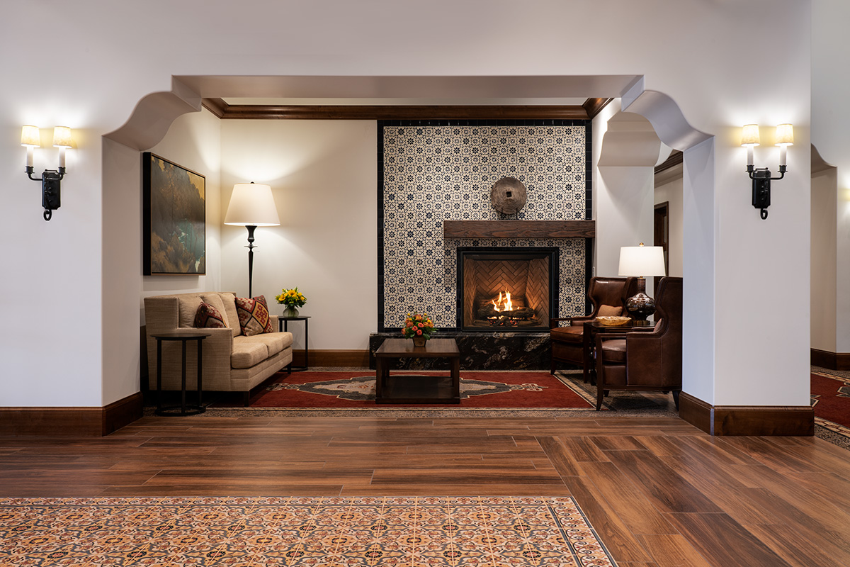 Beautifully decorated living room with a lit fireplace, very spacious and cozy