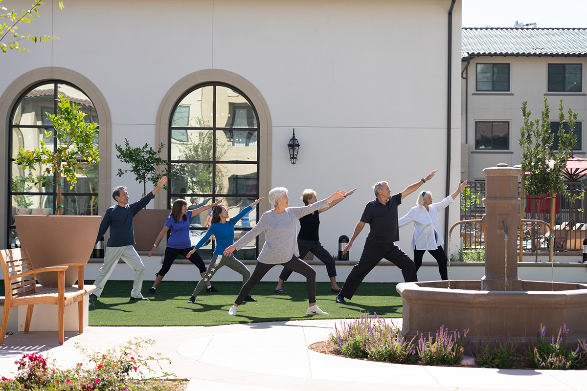 Happy residents doing yoga together in the facility