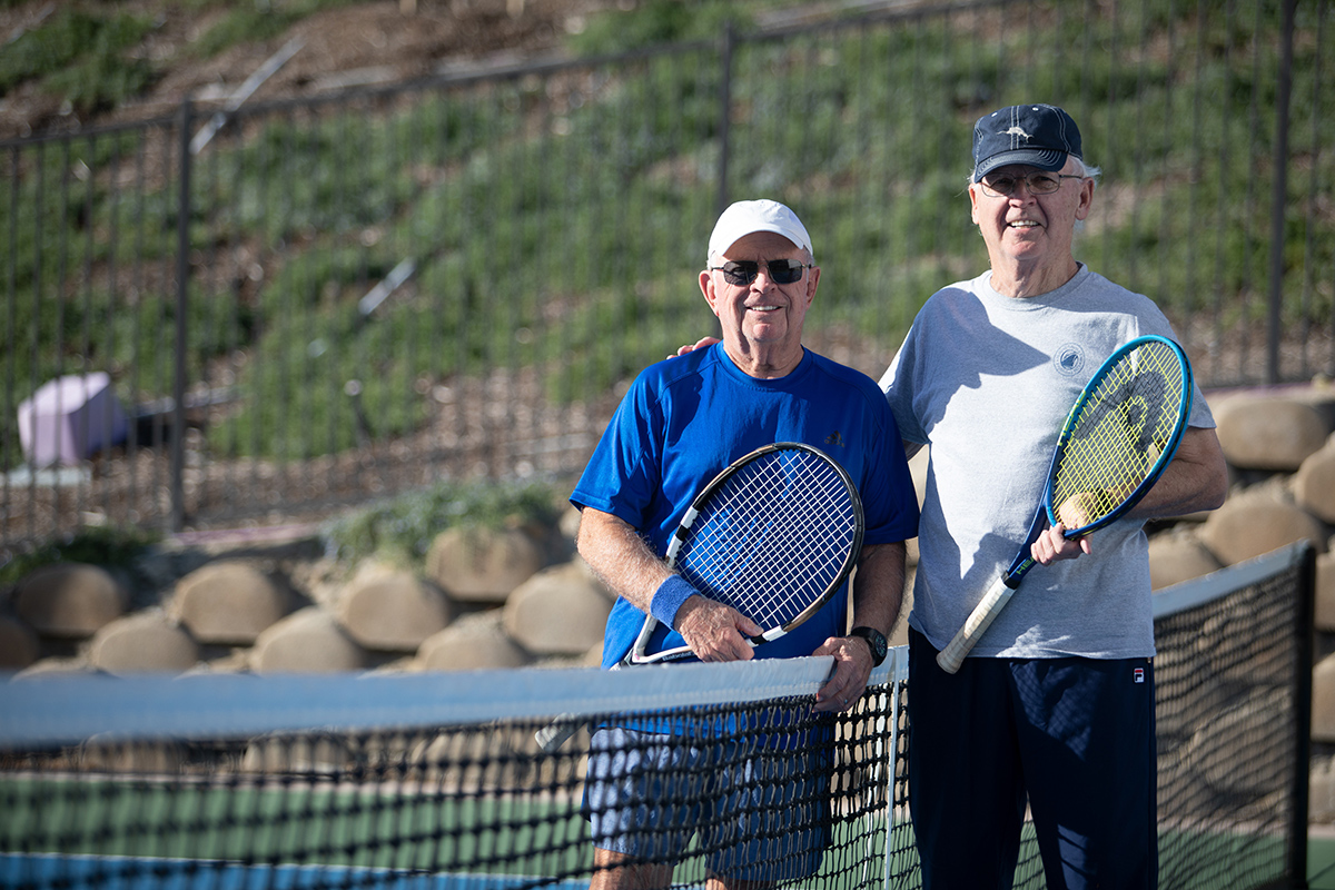 Two residents smiling at the tennis courts with tennis racquets in hand
