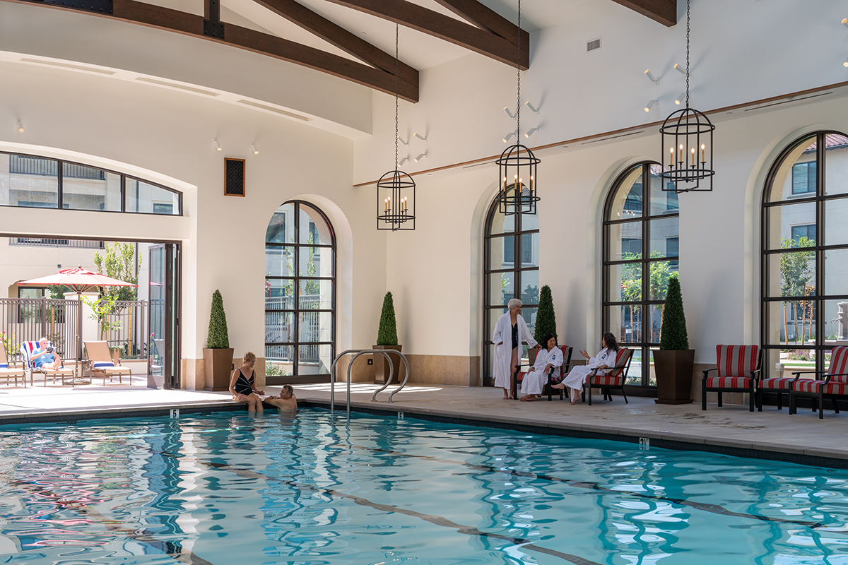 Residents sitting together around the spacious pool