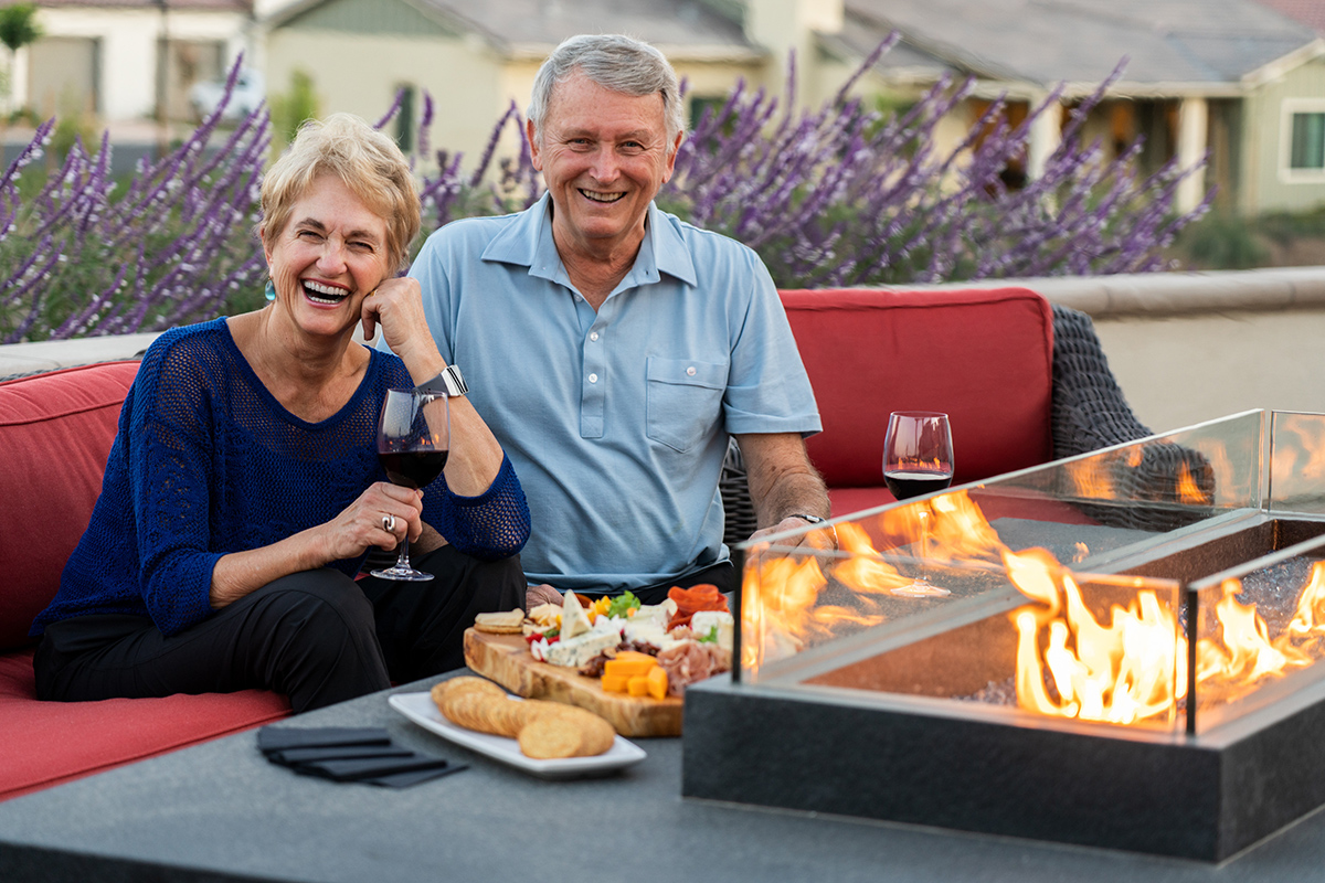 Two people sitting by the fire eating a cheese platter. They both are smiling while enjoying their time outside.