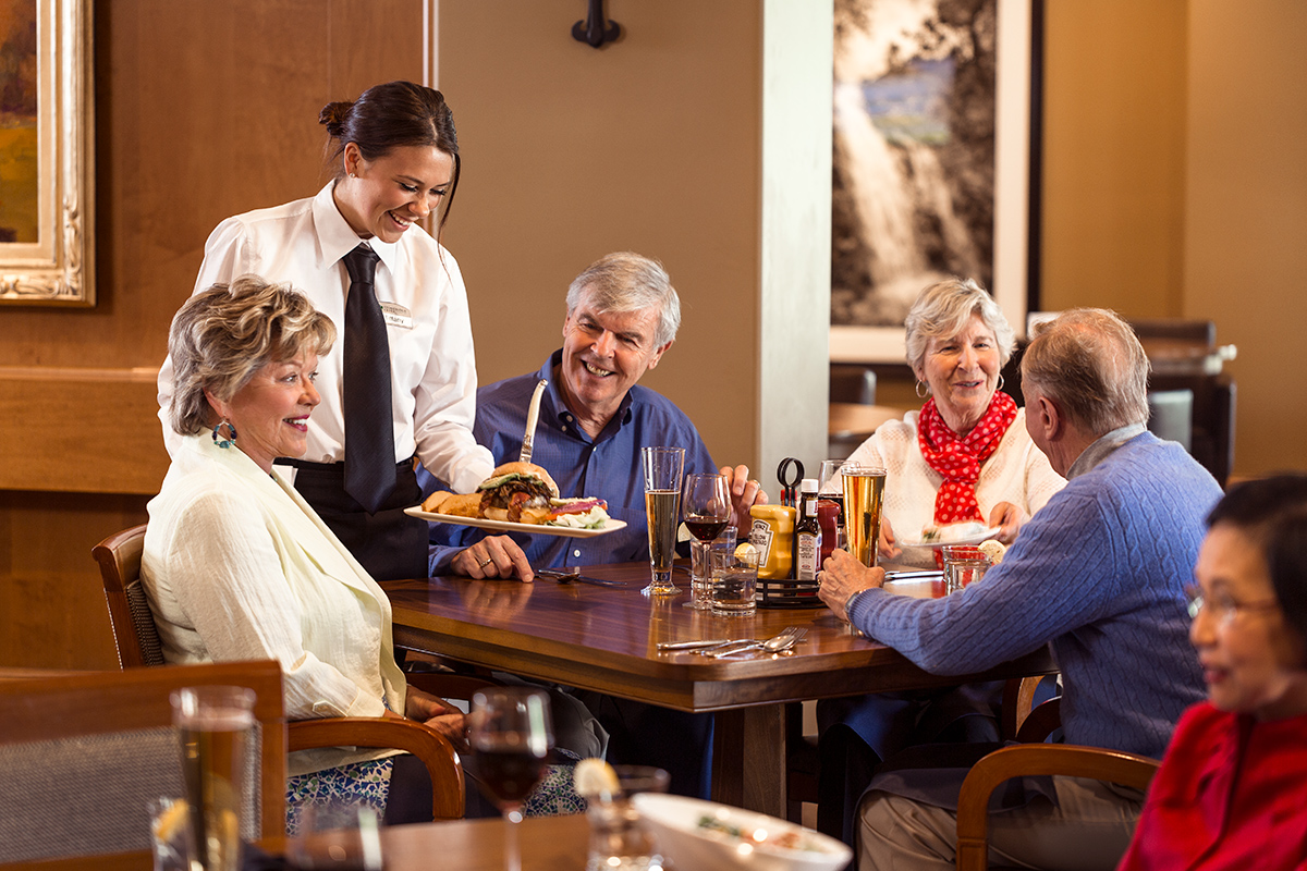 A group of residents being served their meal at a dining table, laughing and smiling
