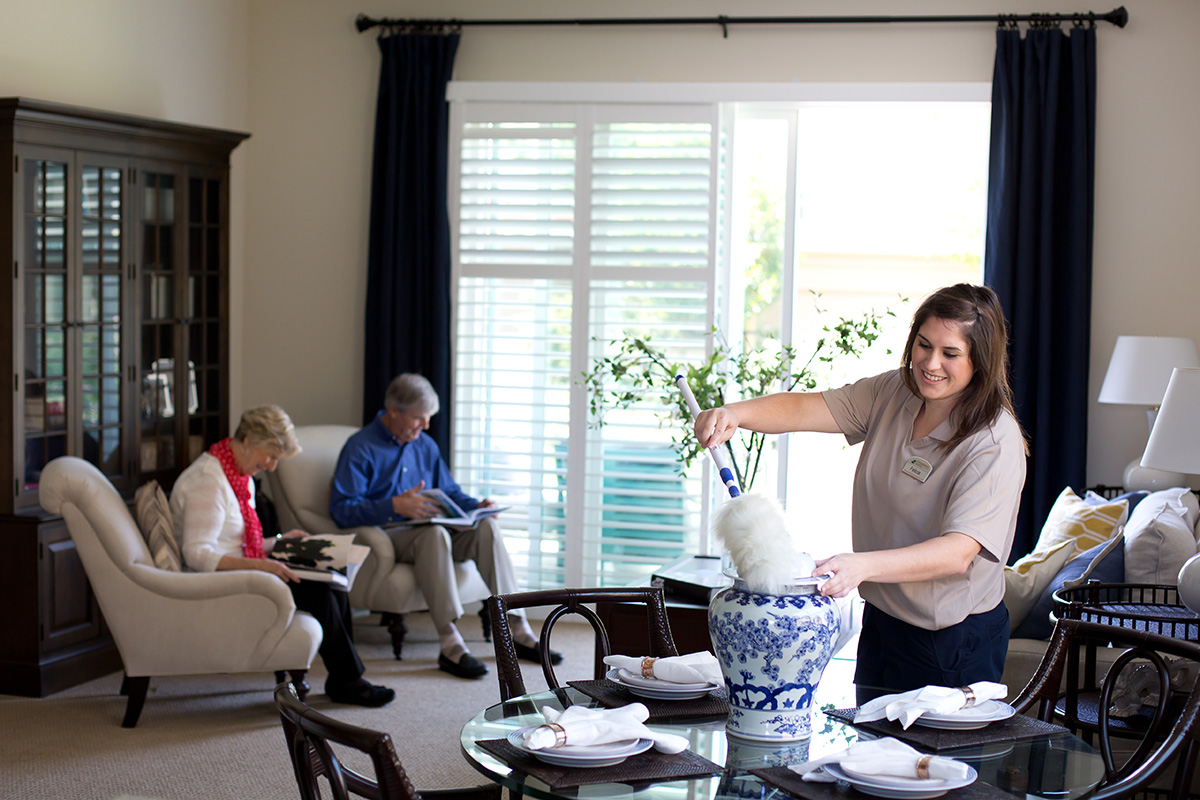 Housekeeping cleaning a residents home while they read books in the background.