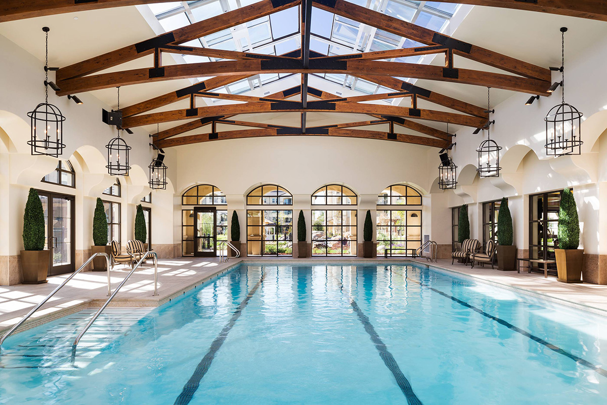 Large pool with wood beams overhead and chandeliers above the walking paths.