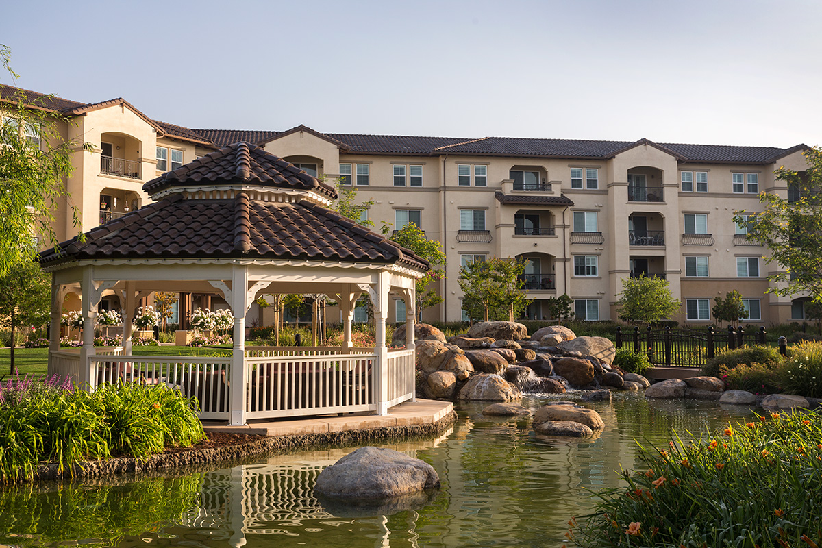 Outside gazebo with seating, large lake with plants and a walking path with the apartments in the background.