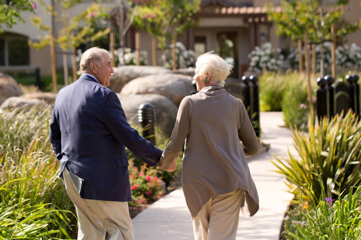 A couple walking hand-in-hand down a walking path lined with plants.