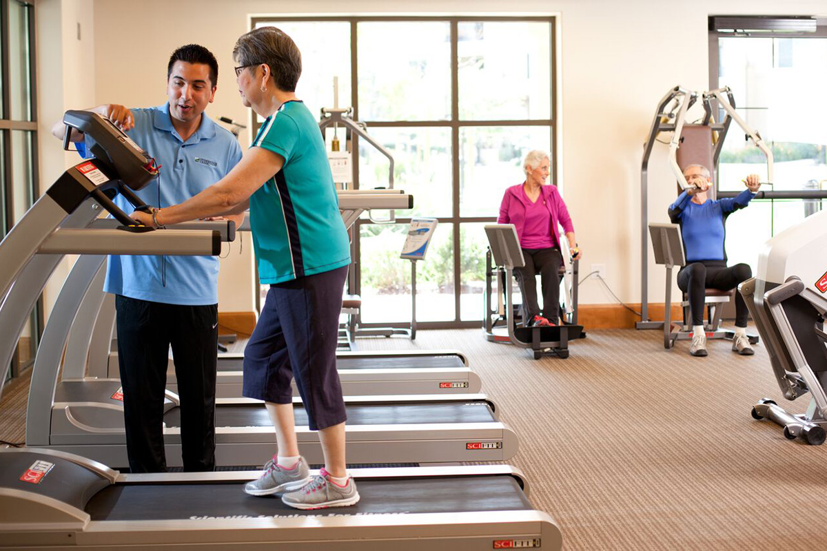 Exercise room with residents actively using the equipment.