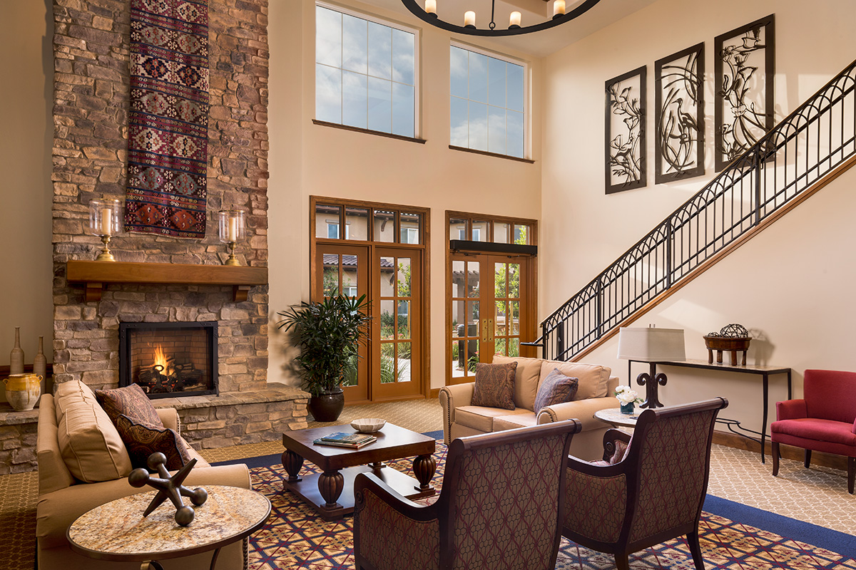 Lobby with vaulted ceilings and large, lit fireplace.