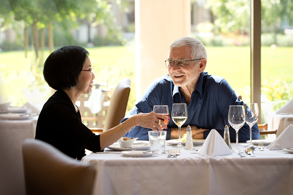 A couple eating together in an elegant dining room.