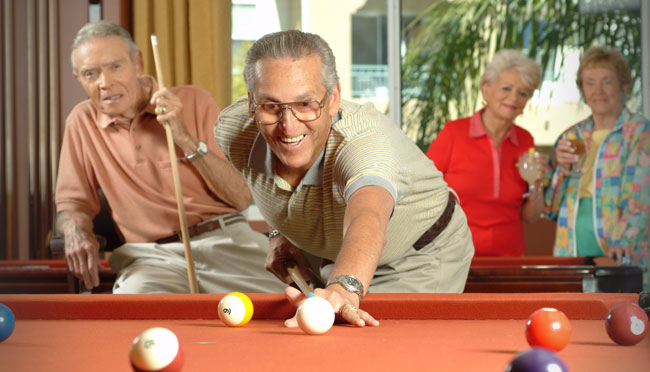Seniors playing a game of pool.