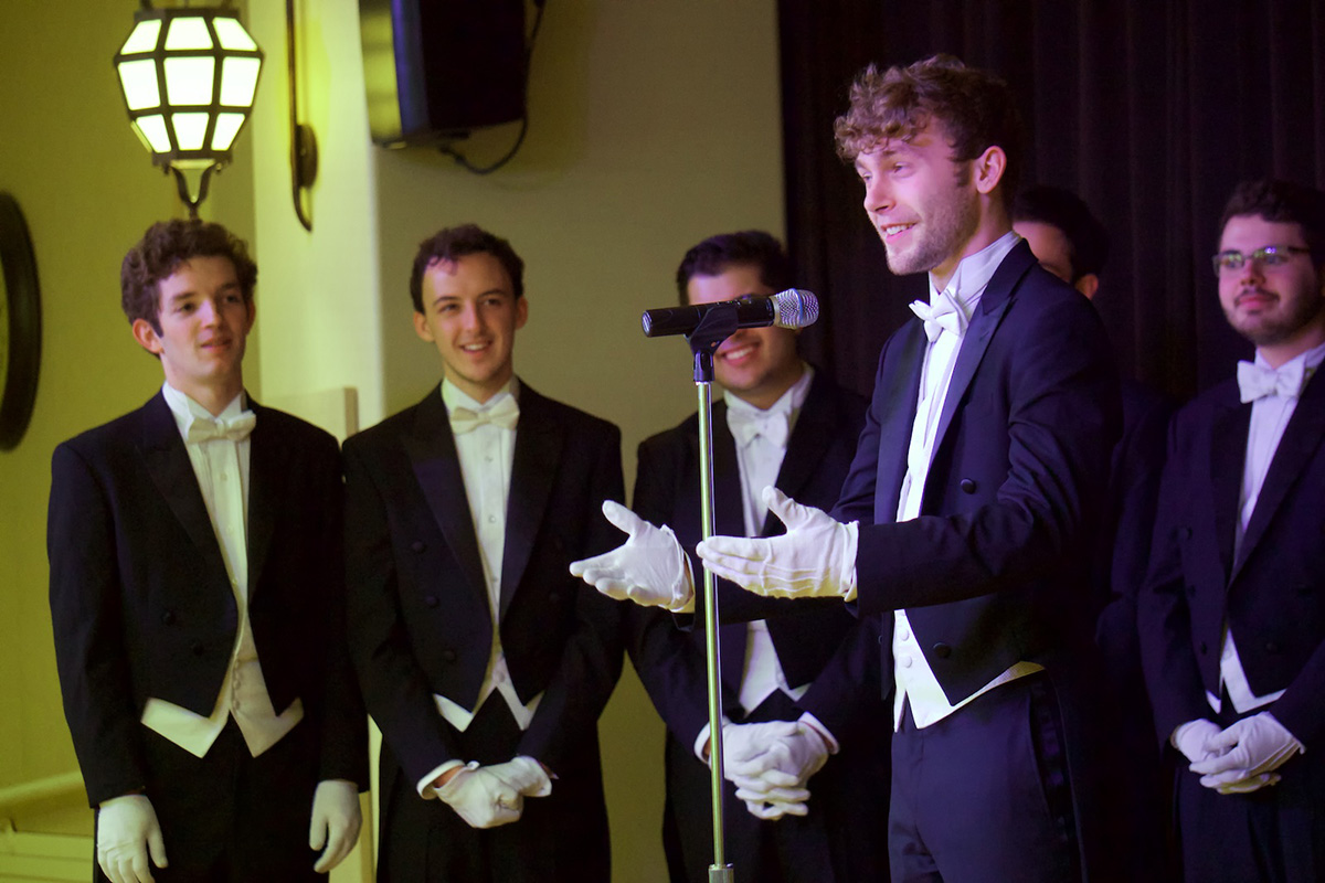 Men in suits singing together on stage.