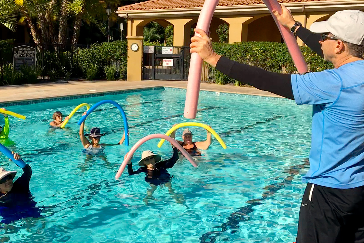Residents in an exercise class in the pool with an instructor.