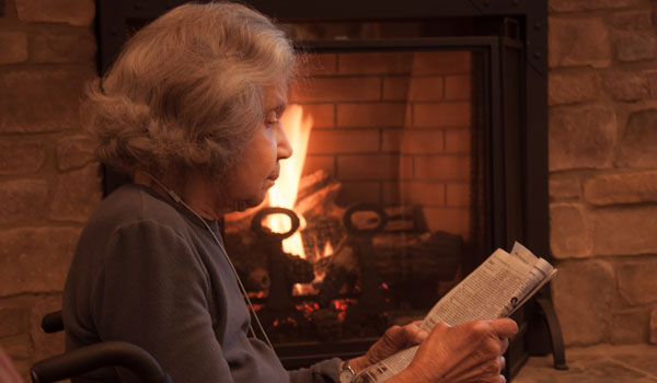 A resident reading the book by a fireplace.
