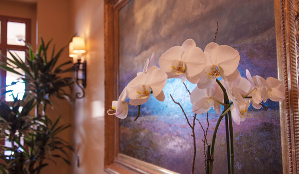 A painting with an orchid flower in front of it.
