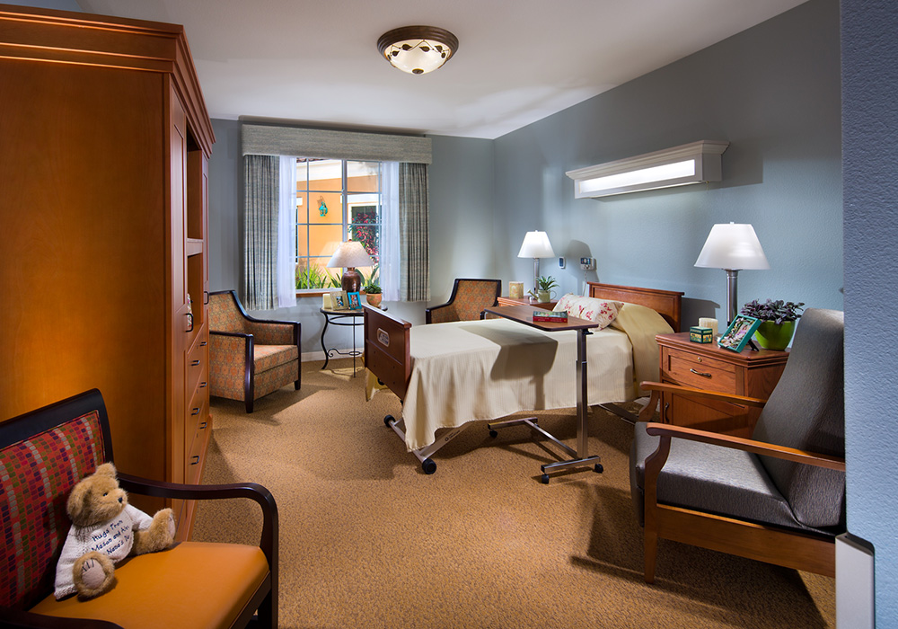 Resident bedroom with seating areas and a large window.