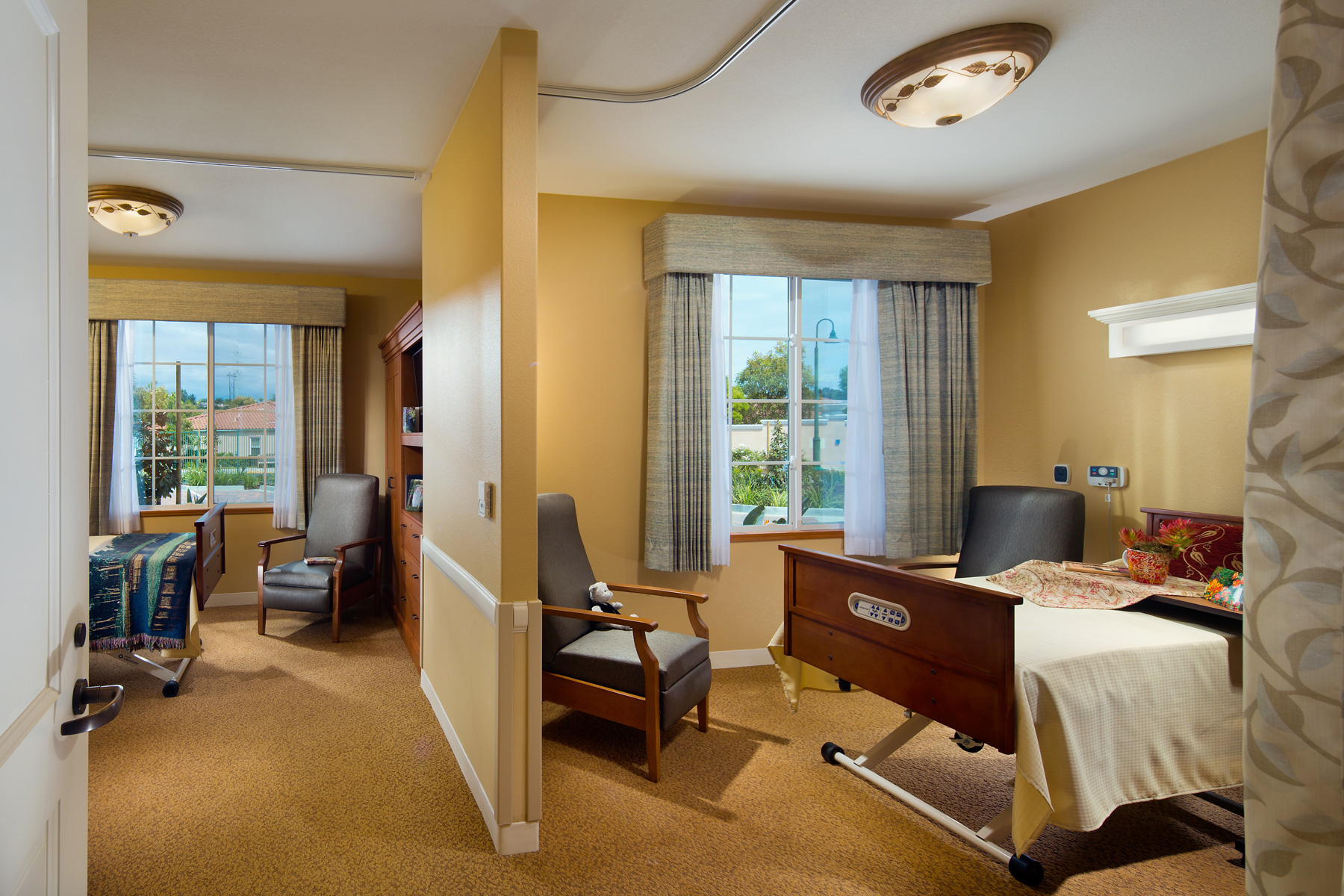 Resident bedrooms with seating and large windows for natural light.