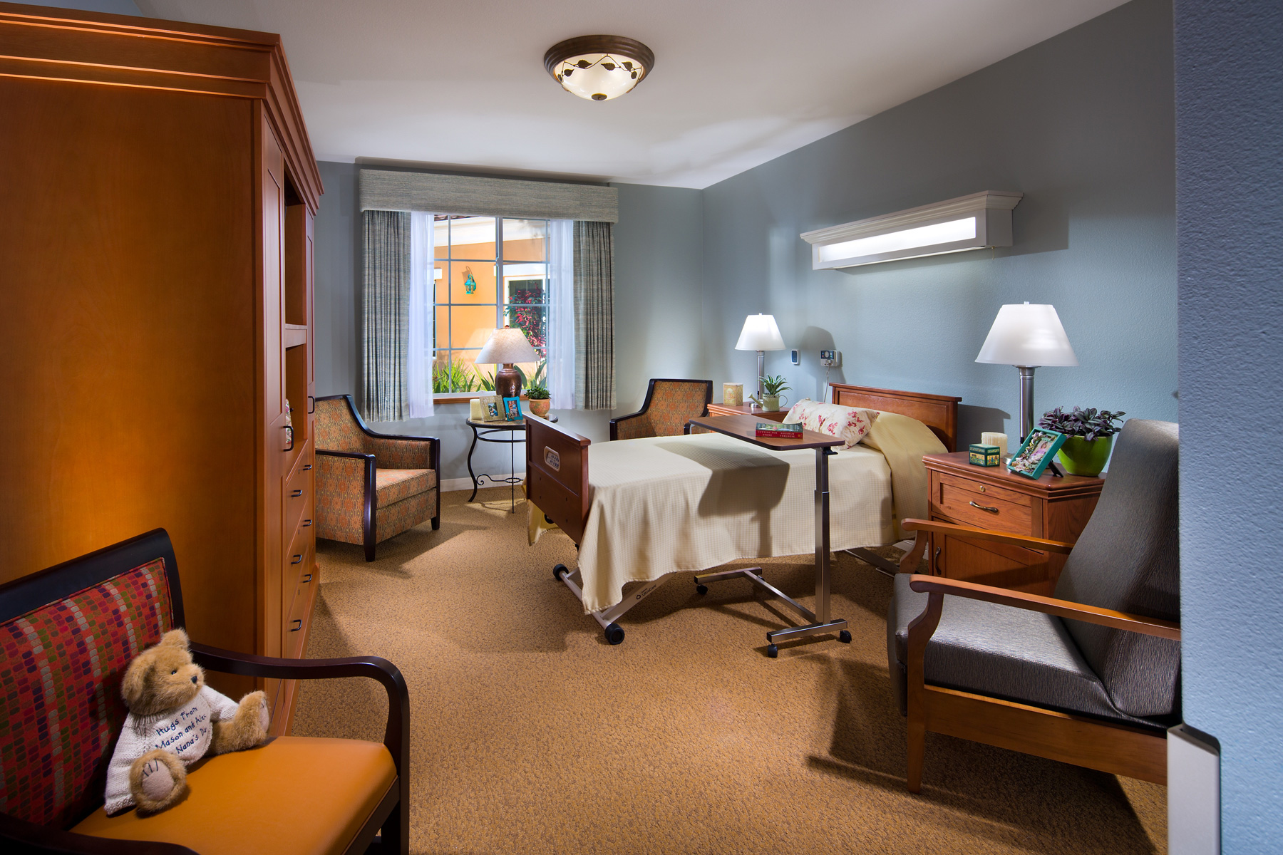 Resident room with seating options, a bed and large window.