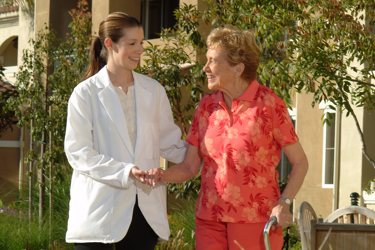 A nurse walking with a resident outdoors.