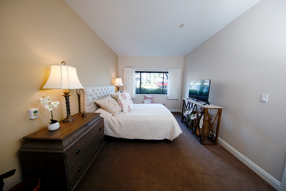 A bedroom with bed, two nightstands, and a tv on a television stand.