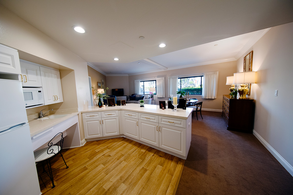 A kitchen area looking out to a dining room and living room.