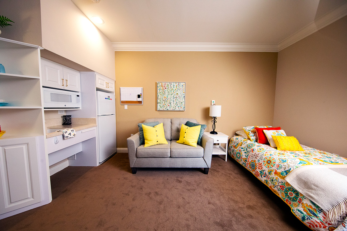 A room with a bed, a small kitchen area and couch.