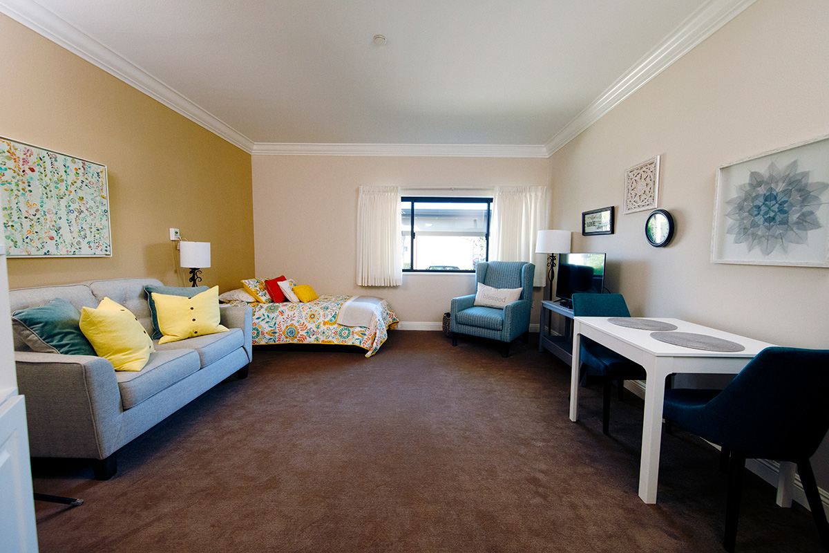A room with dining room table, couch, and bed.