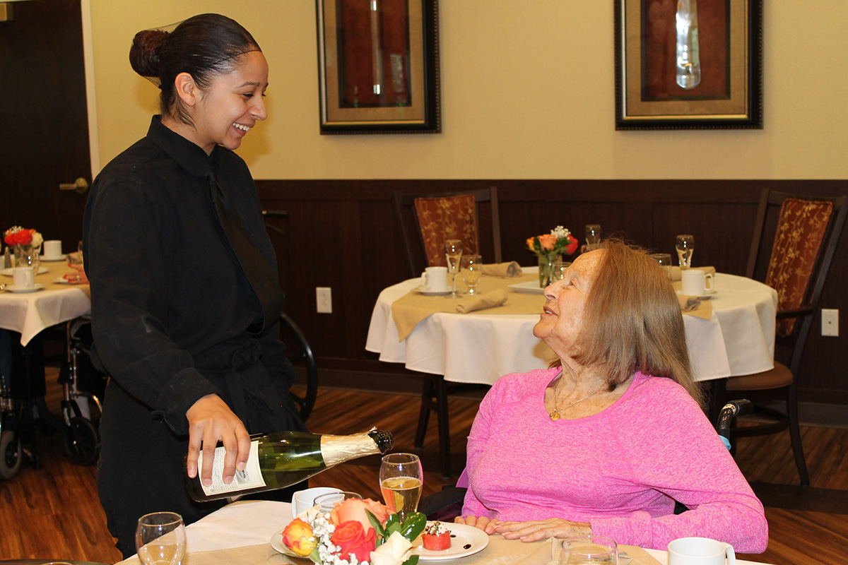 A resident being served a drink with her meal.