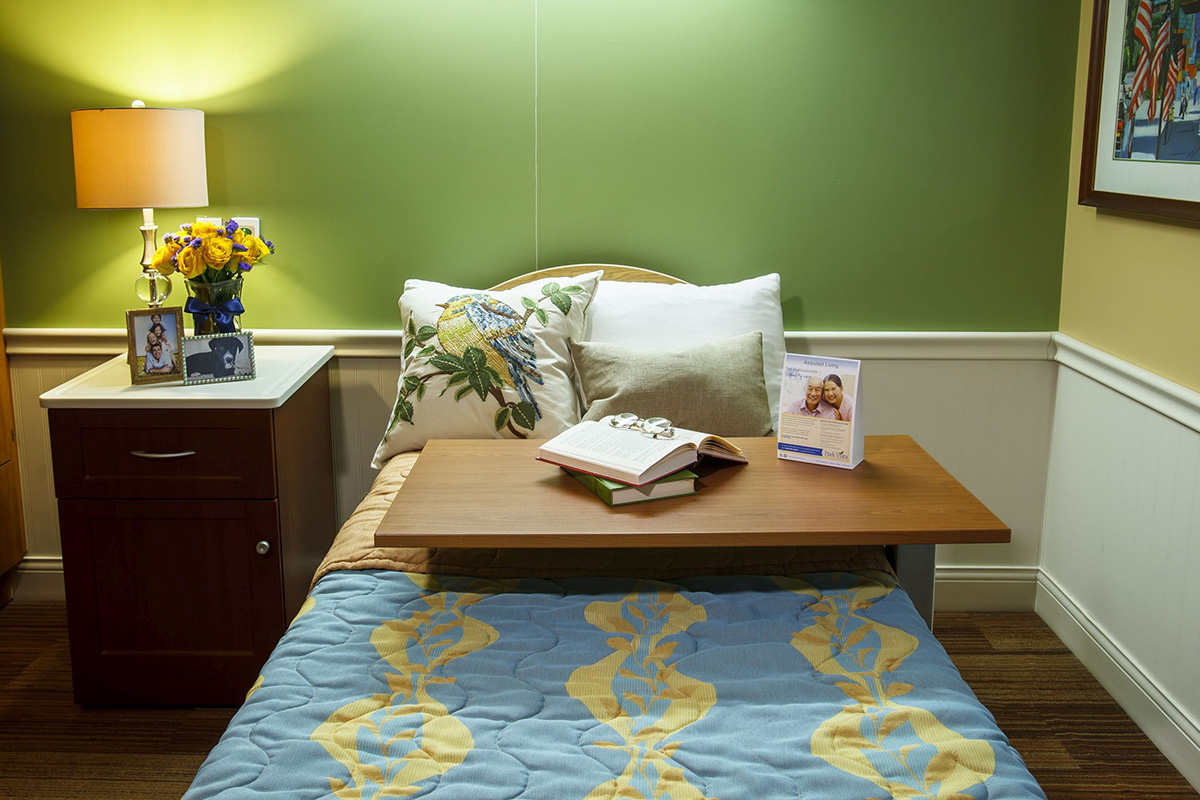 A bed with a nightstand and books on a table.