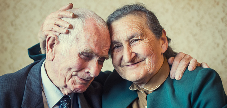 A couple leaning in toward each other smiling.