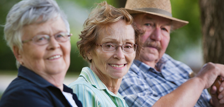 residents sitting on a bench smiling
