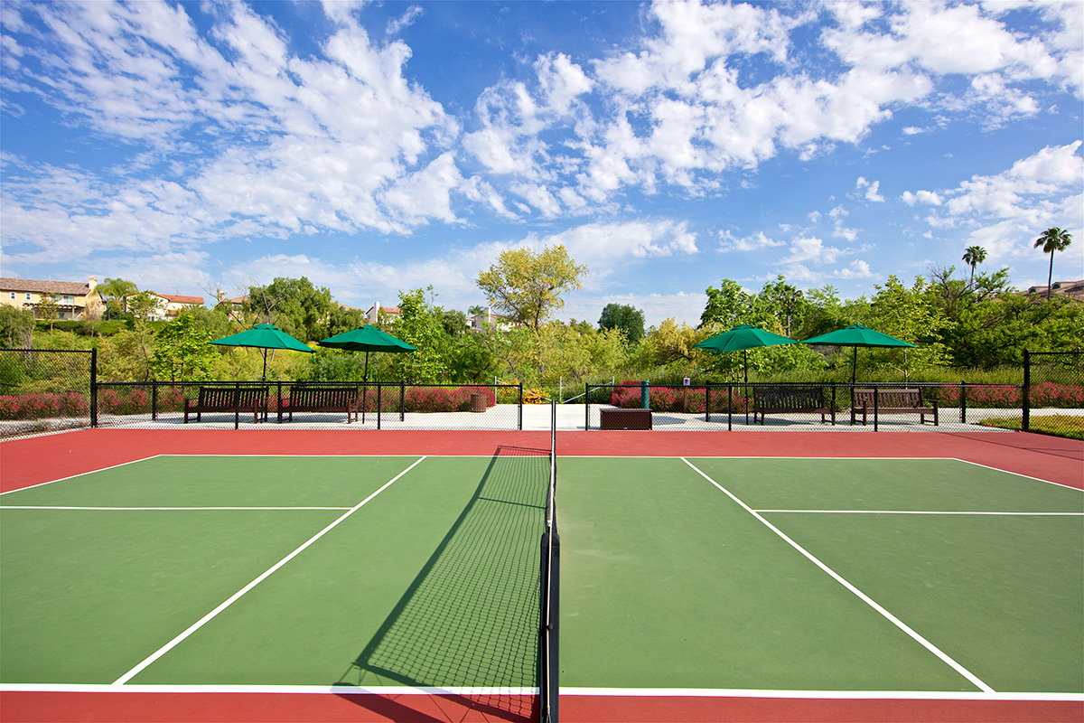 Tennis court with seating beside it.
