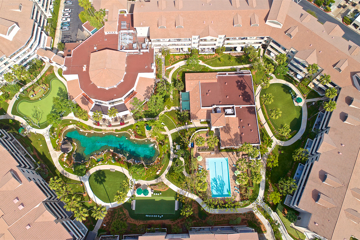 Drone view of the pool, buildings, golf course, pond and apartments.