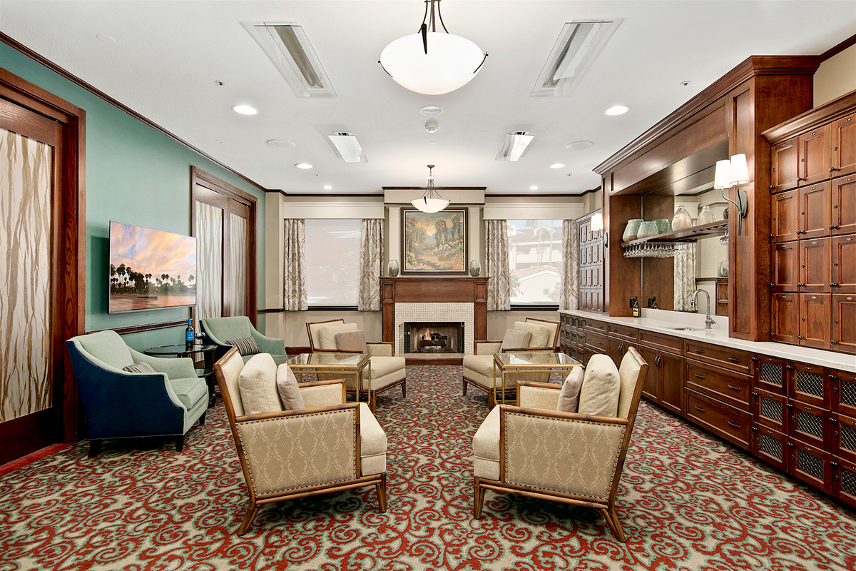 Large common area with fireplace, seating area and sink.