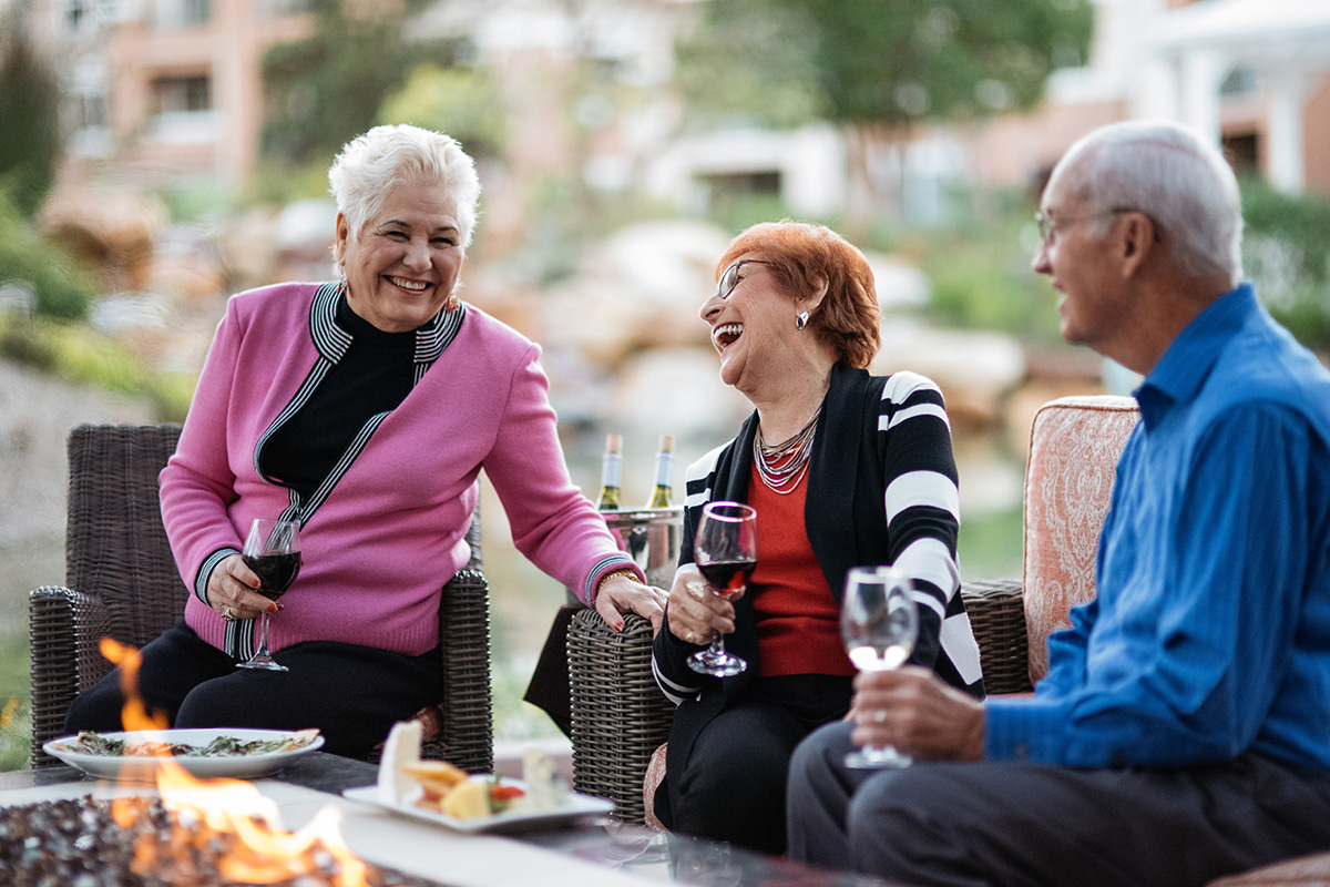 Three people enjoying a drink beside the outdoor fire pit.
