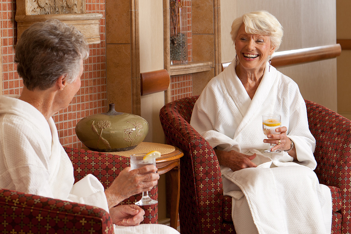 Two women sitting in bathrobes in the spa.