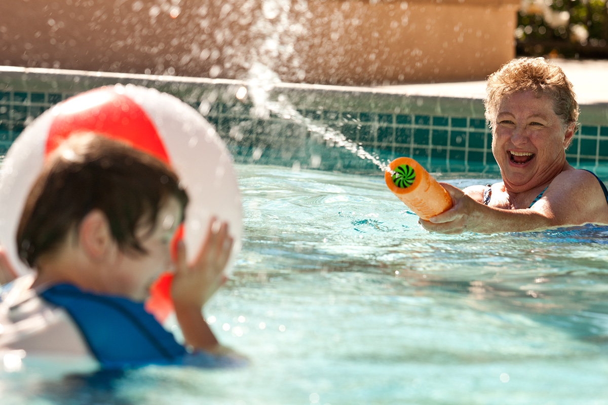 A woman squirting a young boy in the pool.
