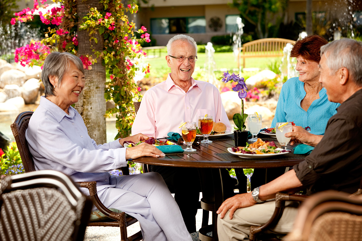 A group of residents eating at an outside table.