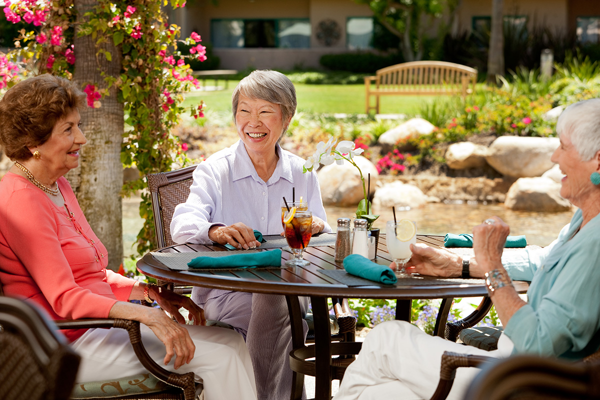 Residents enjoying a cool drink at an outside table.